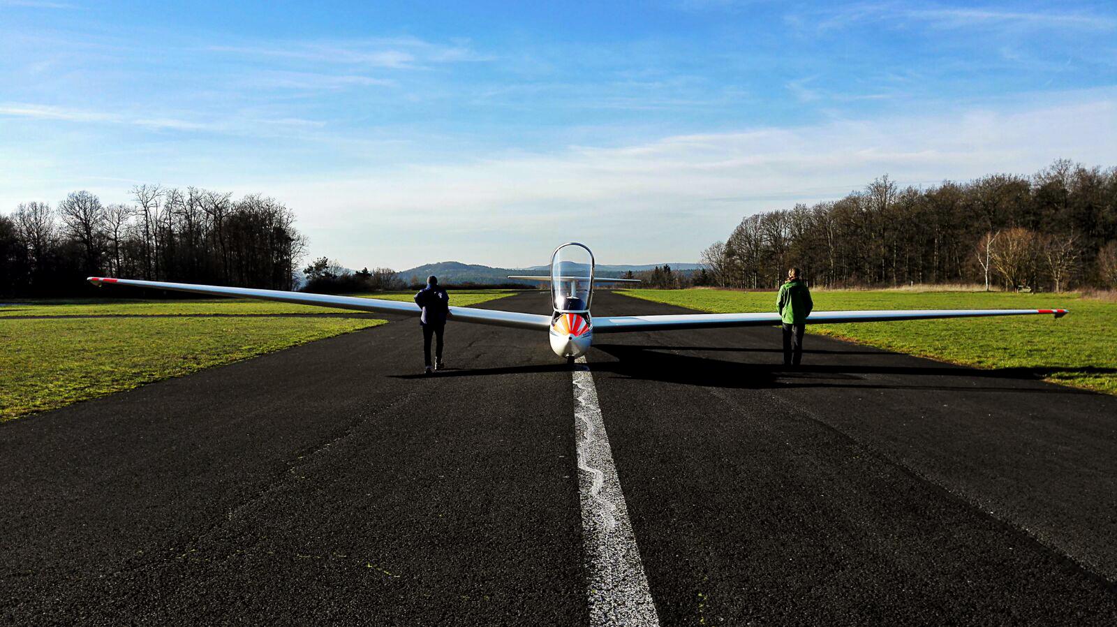 Ein Fluglehrer und ein Schüler schieben die ASK 21 des Vereins zum Startpunkt 09.